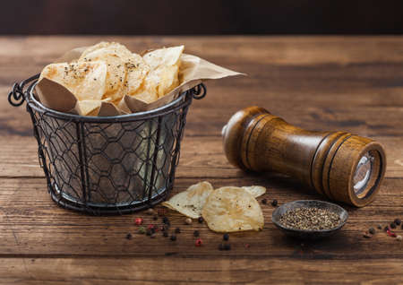Crunchy potato crisps chips with black pepper in steel snack bucket on wooden table background with mill and ground pepper. Reklamní fotografie