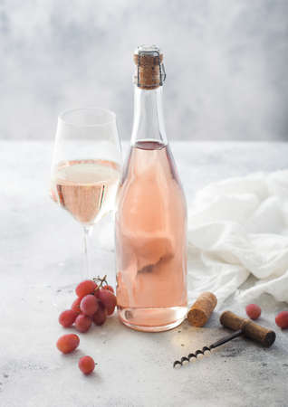 Bottle and glass of pink rose homemade wine with grapes and corkscrew with linen cloth on light table background.