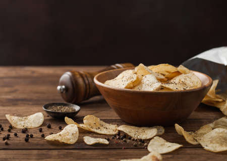 Crunchy potato crisps chips snack with black pepper in wooden bowl on dark table background with mill and ground pepper.
