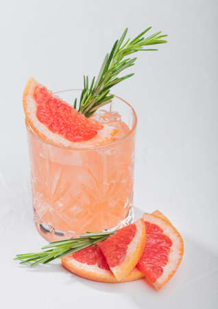 Red grapefruit cocktail with fruit slice and rosemary on white background. Space for text Reklamní fotografie