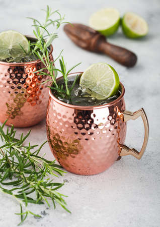 Moscow mule cocktail in a copper mug with lime and rosemary and wooden squeezer on light kitchen table background