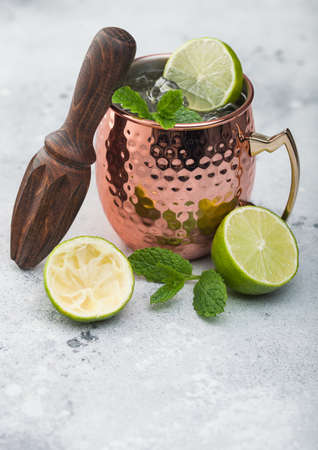 Moscow mule cocktail in a copper mug with lime and mint and wooden squeezer on light kitchen table background