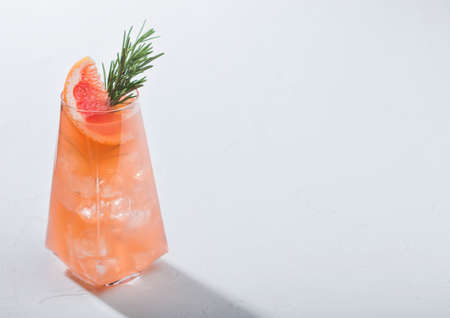 Modern luxury glass of refreshing summer red grapefruit cocktail with ice cubes, fruit slice and rosemary on white background. Space for text