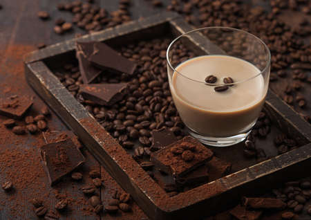 Irish cream baileys liqueur in glass with coffee beans and powder with dark chocolate in wooden tray on dark wood background. Top view Reklamní fotografie
