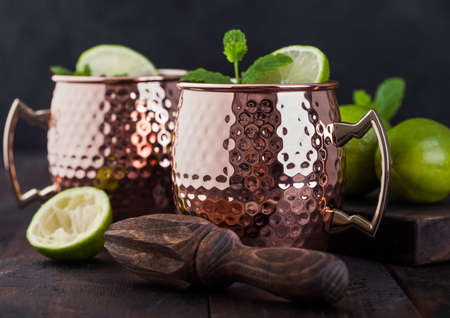 Moscow mule cocktail in a copper mug with lime and mint and wooden squeezer on dark kitchen background.