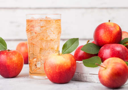 Glass of homemade organic apple cider with fresh apples in box on wooden background, Glass with ice cubes Reklamní fotografie