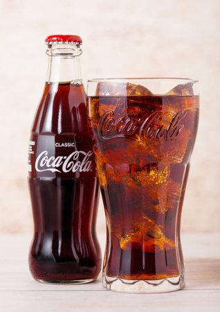 LONDON, UK - AUGUST 03, 2018: Glass bottle and original glass of Original Coca Cola soft drink on wood. Most popular drink in the world. Redakční