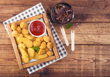 Buttered chicken nuggets and popcorn bites in vintage wooden box with ketchup and glass of cola on wood background. Reklamní fotografie