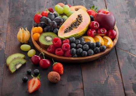Fresh raw organic summer berries and exotic fruits in round wooden plate on dark wooden kitchen background. Papaya, grapes, nectarine, orange, raspberry, kiwi, strawberry, lychees, cherry. Top view Reklamní fotografie