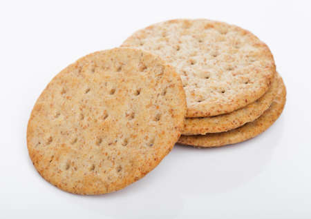 Stack of round organic crispy wheat flatbread salty crackers on white background.