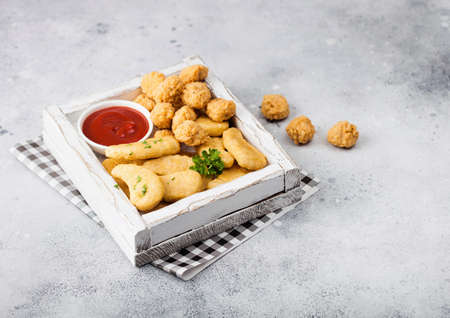Buttered chicken nuggets and popcorn bites in white vintage wooden box with ketchup on light background. Fast food snack bar.