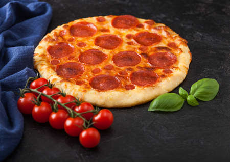 Fresh round baked Pepperoni italian pizza with tomatoes with basil on black kitchen table background. Reklamní fotografie
