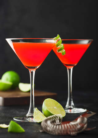 Cosmopolitan cocktail in classic crystal glasses with lime peel and fresh limes with strainer on black table background. Stock Photo