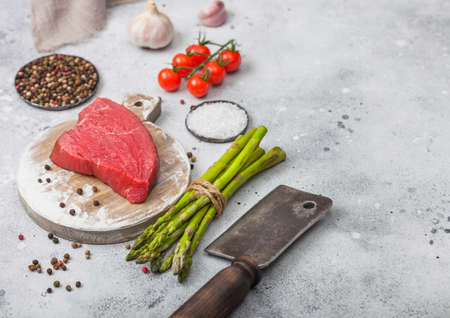 Slice of Raw Beef sirlion steak on round chopping board with tomatoes,garlic and asparagus tips and meat hatchet on light kitchen table background.