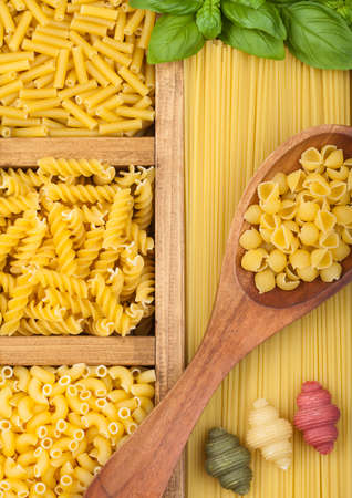Box with spaghetti and fusilli and macaroni with maccheroni and fresh basil with wooden spoon and tricolor conchigiolli as italian flag Top view Фото со стока