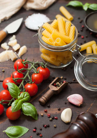 Fresh raw penne pasta in glass jar with tomatoes and basil, garlic and oil with parmesan cheese and salt and pepper on wooden background.Top view Фото со стока