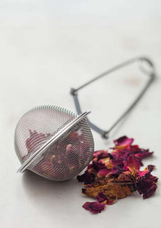 Rose petals craft grade tea with strainer infuser on white background.