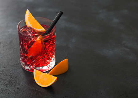 Negroni cocktail in crystal glass with orange slice and black straw on black table background. Top view Фото со стока