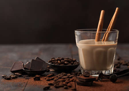 Crystal glass of Irish cream liqueur with cinnamon, coffee beans and powder with dark chocolate on dark wood background. Space for text Фото со стока