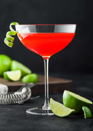 Cosmopolitan cocktail in luxury crystal glass with lime peel and fresh limes with strainer on black table background. Фото со стока