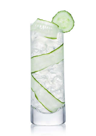 Fresh cold cucumber water in highball glass with ice cubes and cucumber slices on white background. Healthy and refreshing organic drink.