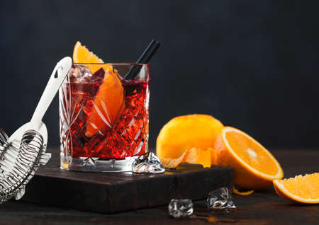 Negroni cocktail in crystal glass with orange slice and fresh raw oranges on chopping board with strainer on wooden background. Фото со стока