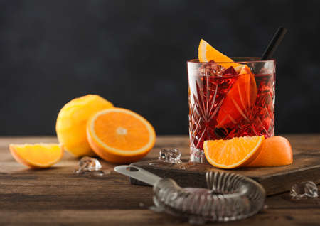 Negroni cocktail in crystal glass with orange slice and fresh raw oranges on chopping board with strainer on wood background. Top view