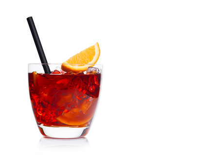 Negroni Cocktail in luxury glass with ice cubes and orange slices with straw on white background. Space for text