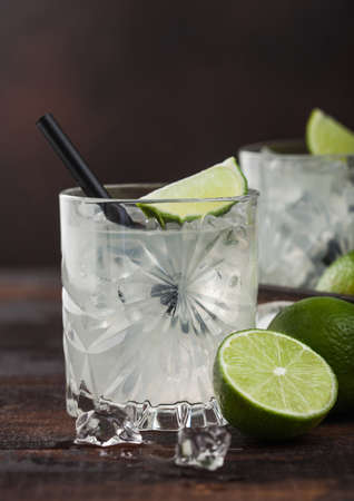 Gimlet Kamikaze cocktail in crystal glass with lime slice and ice on wooden background. Фото со стока