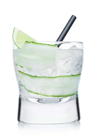 Gimlet cocktail in modern glass with ice cubes and straw, cucumber and lime slice on white background.