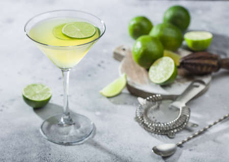 Gimlet Kamikaze cocktail in martini glass with lime slice and ice on light background with fresh limes and strainer with shaker.