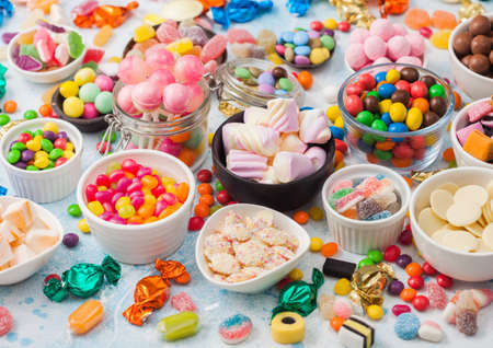 Milk chocolate and jelly gums candies on blue with liquorice allsorts and strawberry bonbons and large variety of sweets and candies. Top view Фото со стока