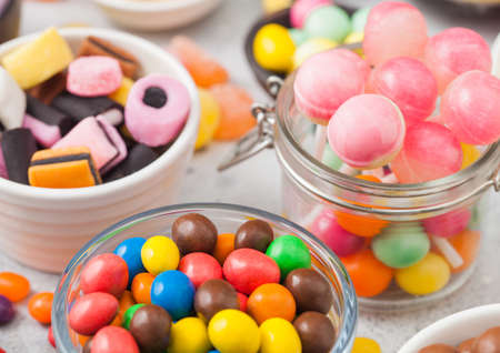 Pink lollipop candies in jar with various milk chocolate on white table background with liquorice allsorts