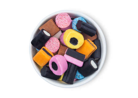 Liquorice Allsorts Sweets mixed in white ceramic plate on white background. Top view