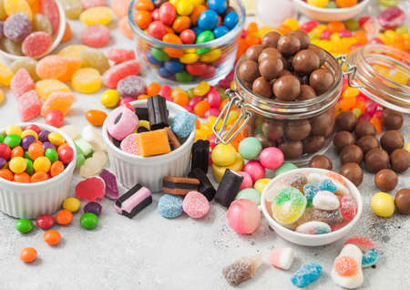 Milk chocolate candies woth shell in jar with various jelly gums candies on white table with liquorice allsorts and strawberry bonbons with different sour sugar gums. Фото со стока