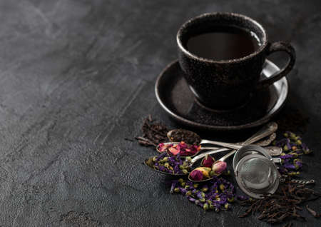 Tea cup with spoons and various tea on black. Black and green loose tea,rose buds,blue mallow flowers