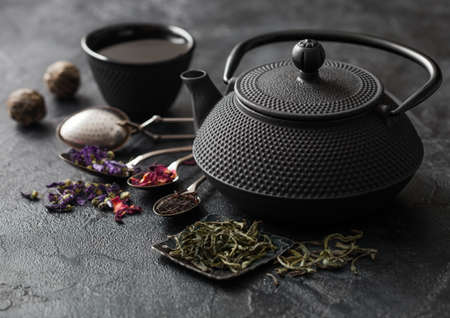 Chinese teapot with cup and infuser with various tea on black. Rose buds,blue mallow flowers,green and black loose tea Фото со стока