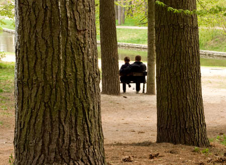 secretly: The loving couple sits on a bench in spring park Stock Photo