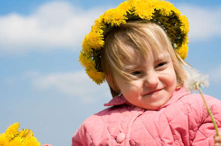 Portrait of the little girl with a wreath from dandelions on a head photo