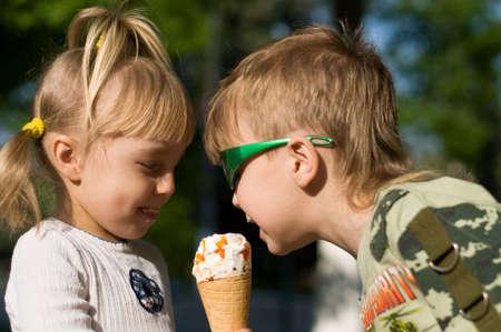 Small children in a summer garden eat cold icecream