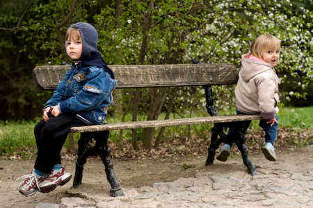 The offended boy and the girl sit on a bench in park Stock Photo - 4904146