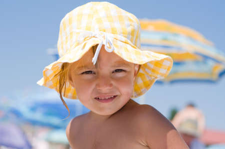 Beautiful little girl with sun hat on beach Stock Photo
