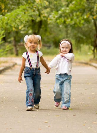 Young girl-friends go for a walk the park photo