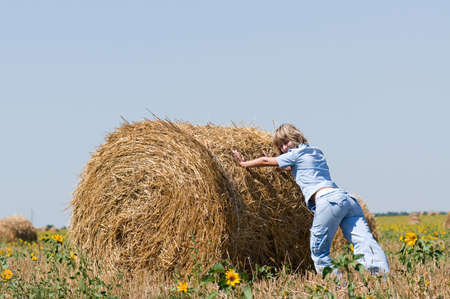 Haystack and girl on the meadow in sunny day photo