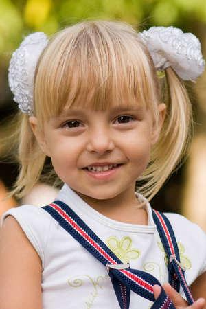 waiting glance: Portrait of little beautiful girl wearing suspenders Stock Photo
