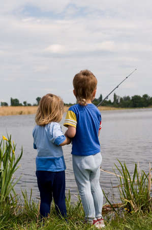 Little boy and girl fishing on the lake photo