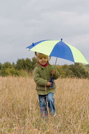 Little girl with her umbrella in autumn day