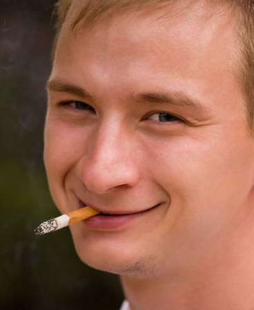 A young man smoking cigarette, focus is set at his face Stock Photo - 5675874