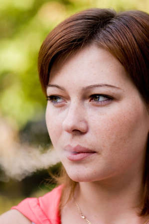 women smoking: Young woman blowing smoke in the air Stock Photo