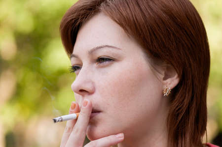 pernicious: The young woman who is smoking a cigarette and carrying away a smoke in air